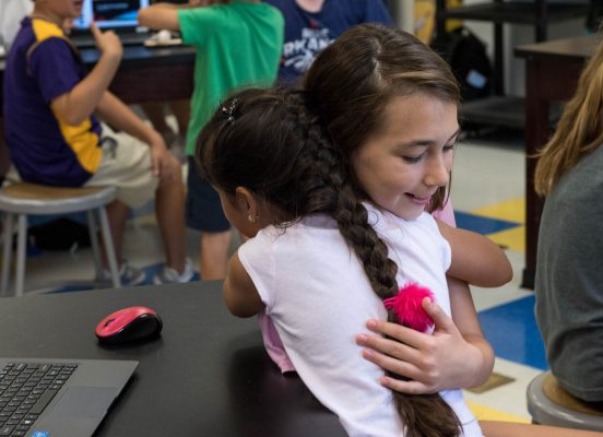 children-hugging-in-class