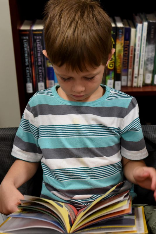little-boy-reading-in-a-library