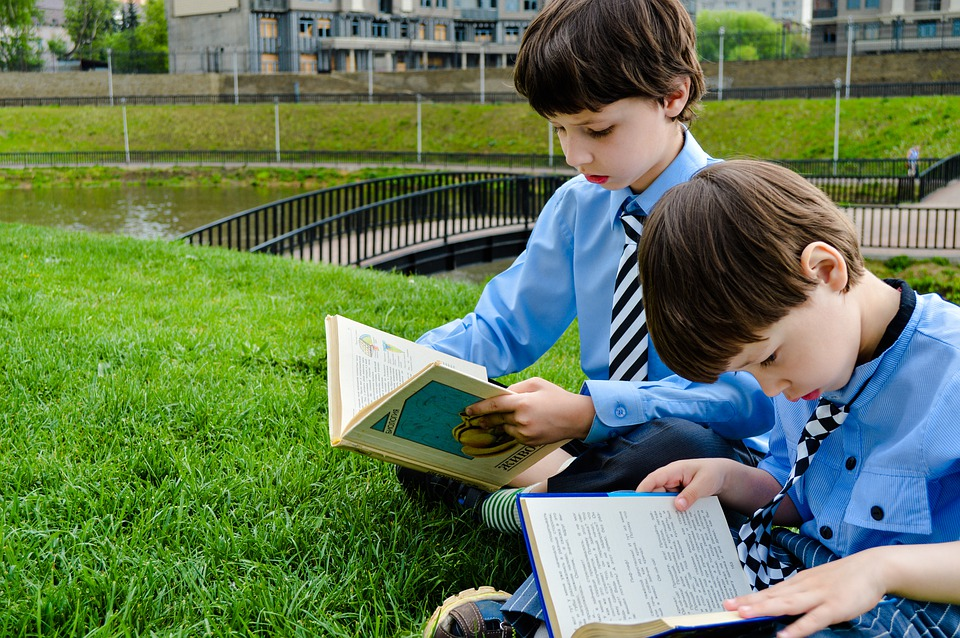 boys-reading-on-the-grass