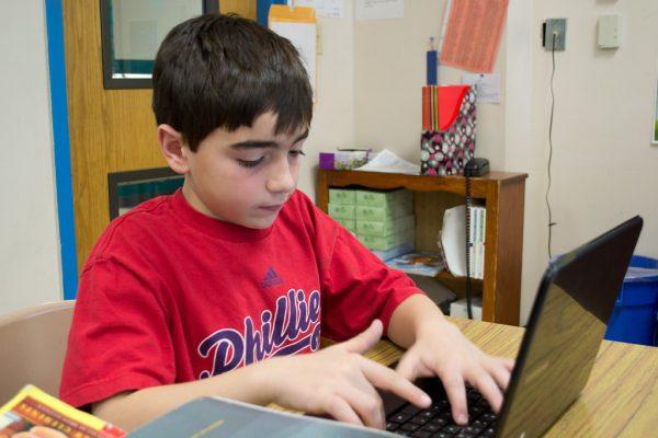 a-boy-typing-on-laptop